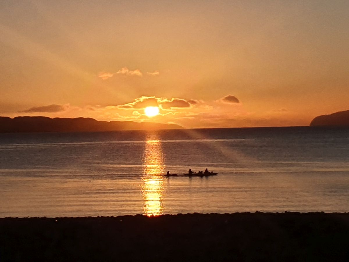 Tralee beach with kayaks at sunset